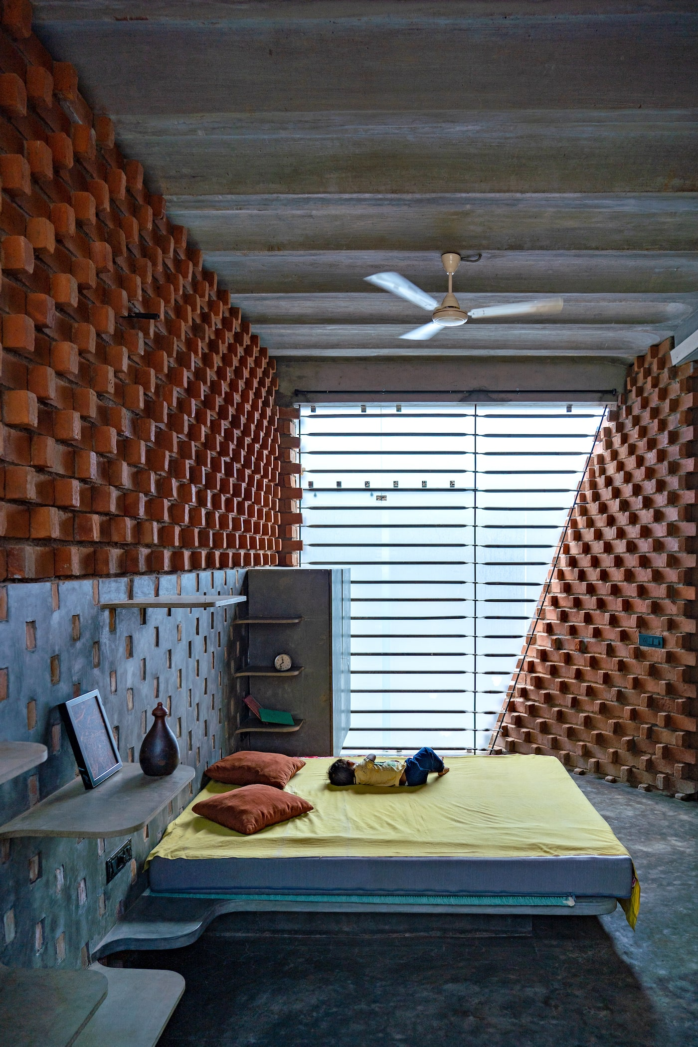Bedroom with concrete floors and red brick walls