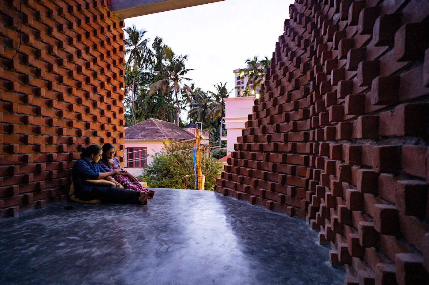 Woman sitting on concrete floor looking out through brick walls of Pirouette House