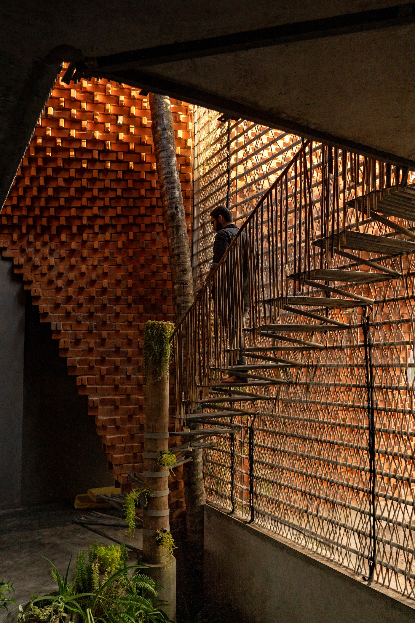 Man walking down metal staircase next to bamboo privacy screen