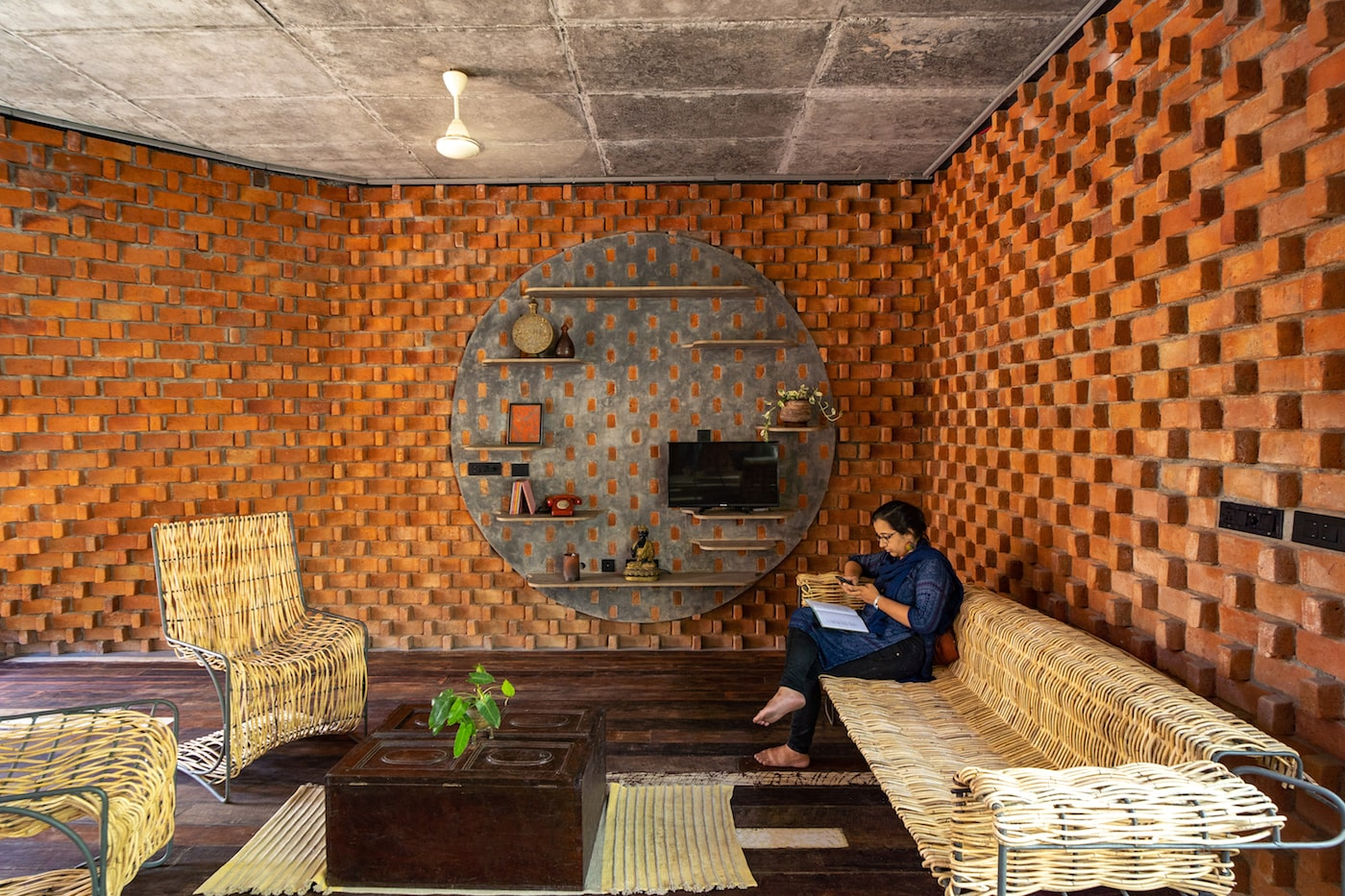 Woman sitting on cane lounge in brick home