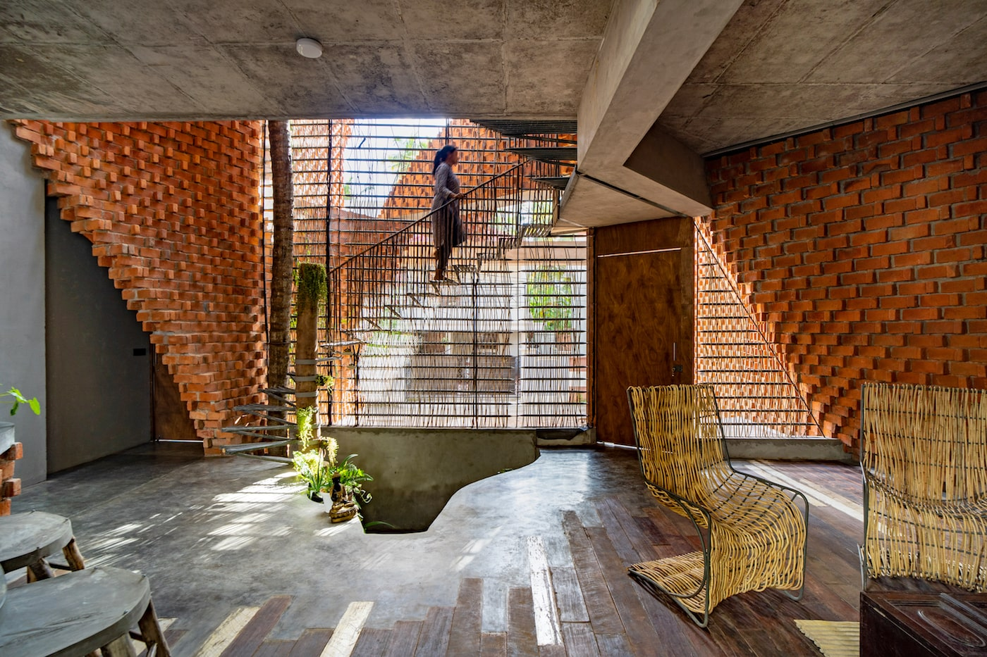 Woman walking up metal staircase inside brick and concrete home