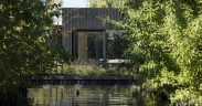 Black timber tiny home with pond