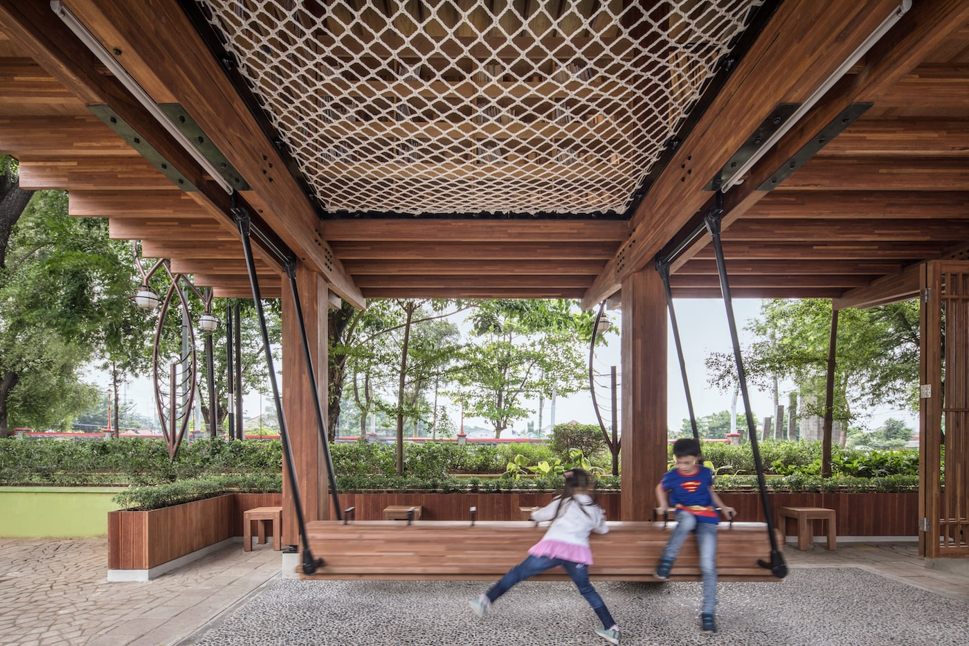Kids playing on timber swing underneath timber library