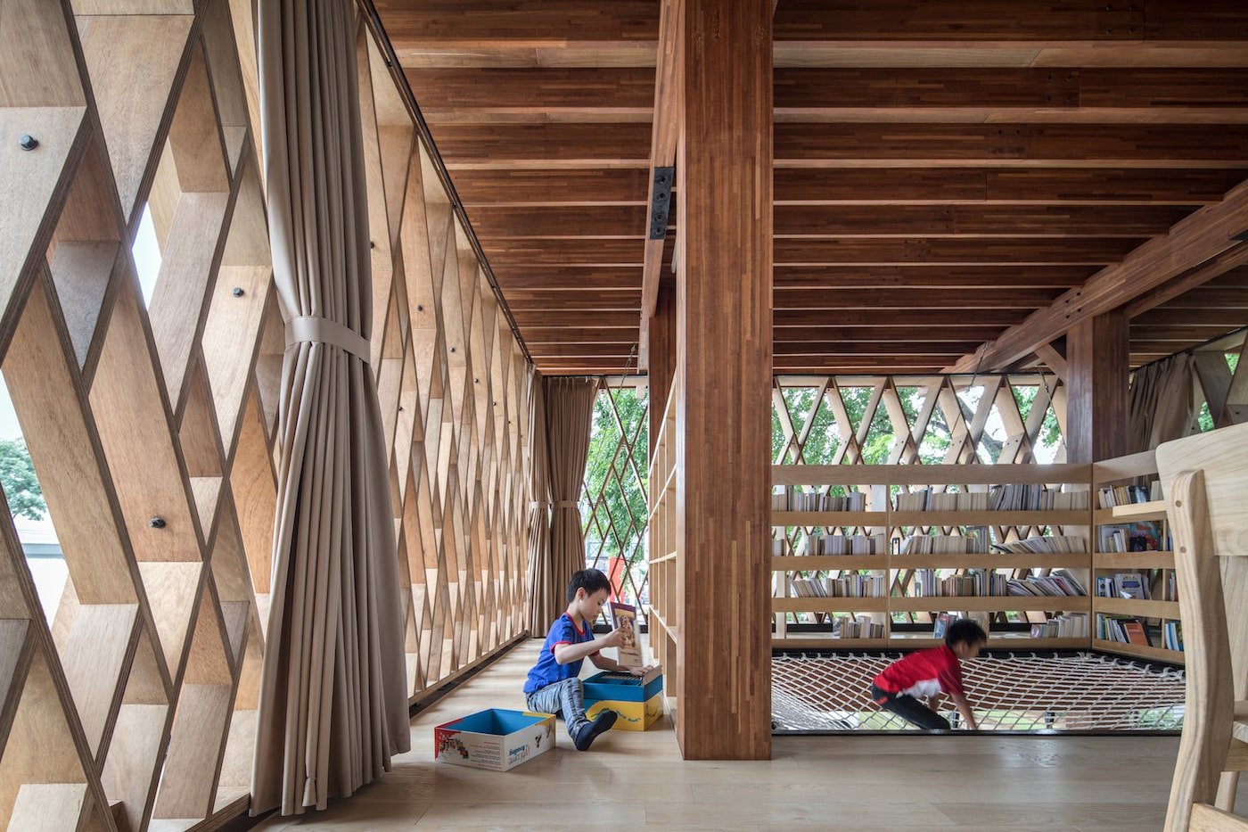 Kids playing next to books in timber library