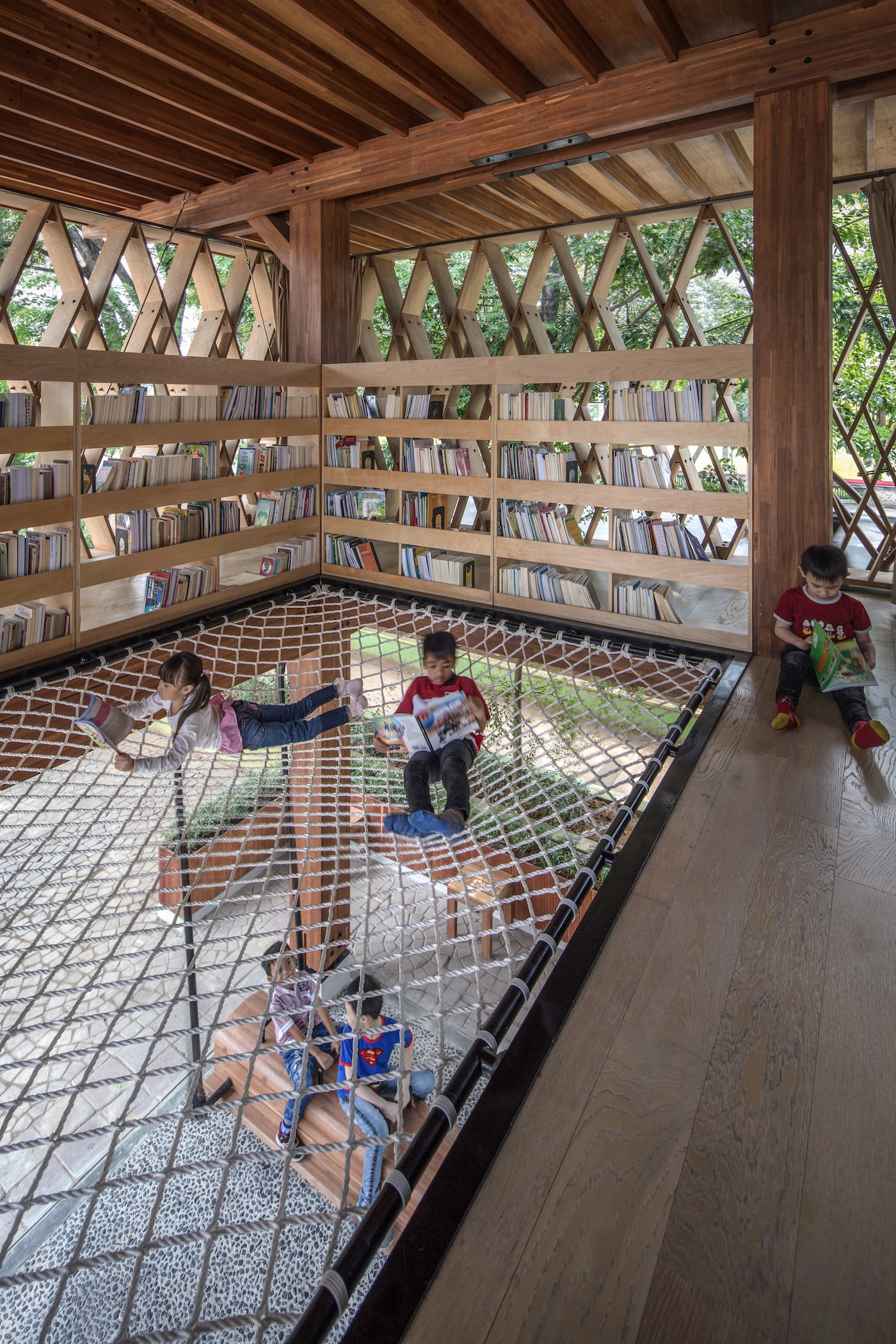 Kids reading on rope hammock floor in timber library