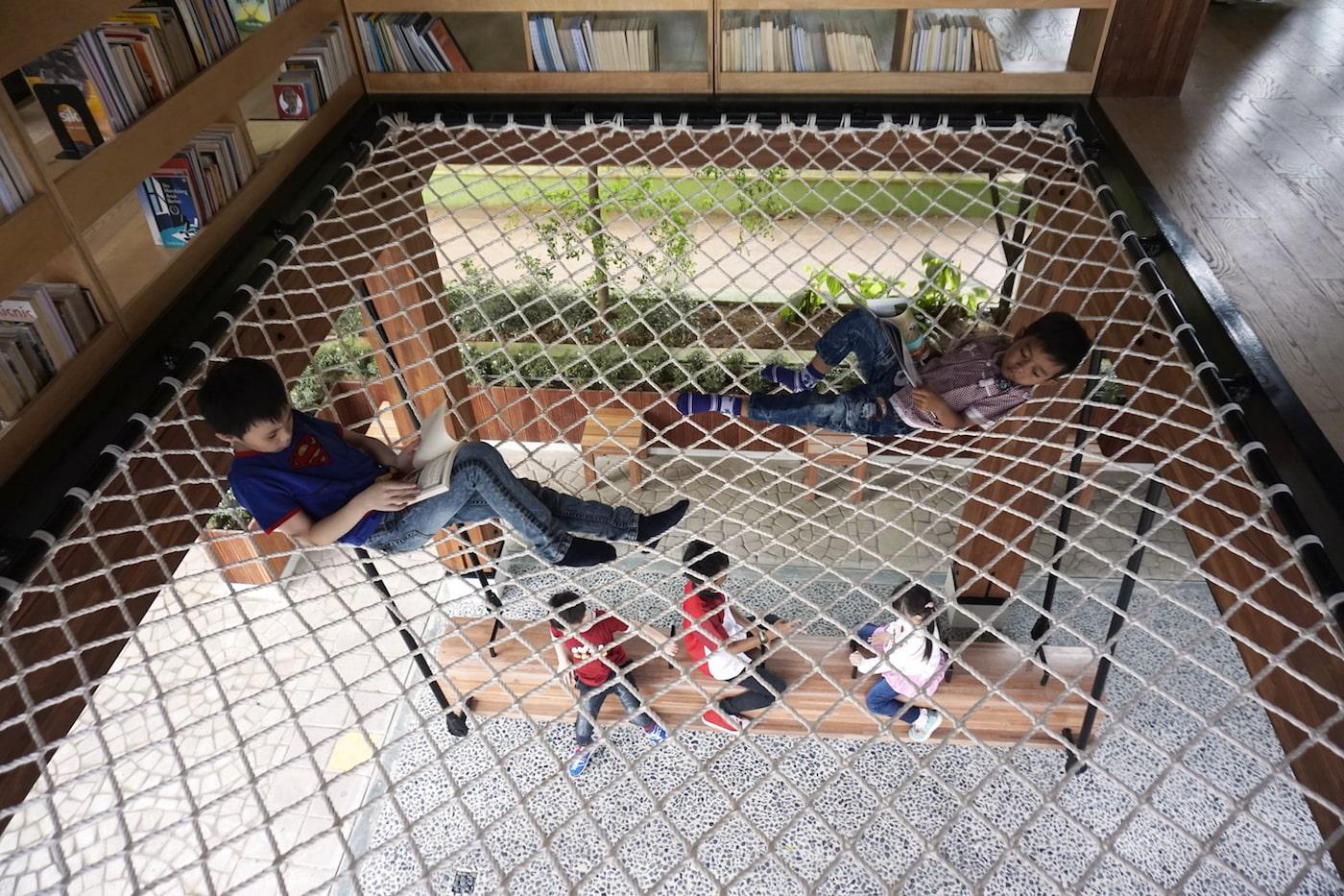 Kids sitting on rope hammock floor with kids sitting underneath