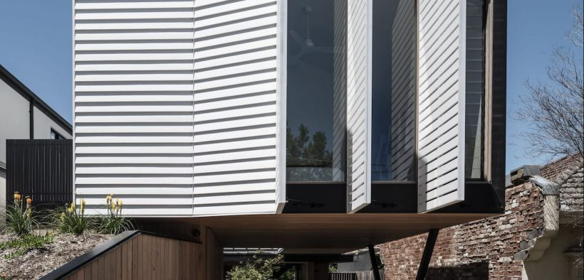 White operable screens on house facade
