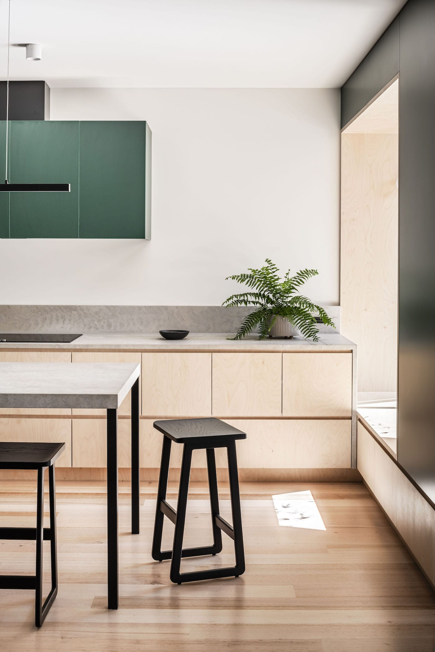 Close up of kitchen with birch plywood and green with barstools