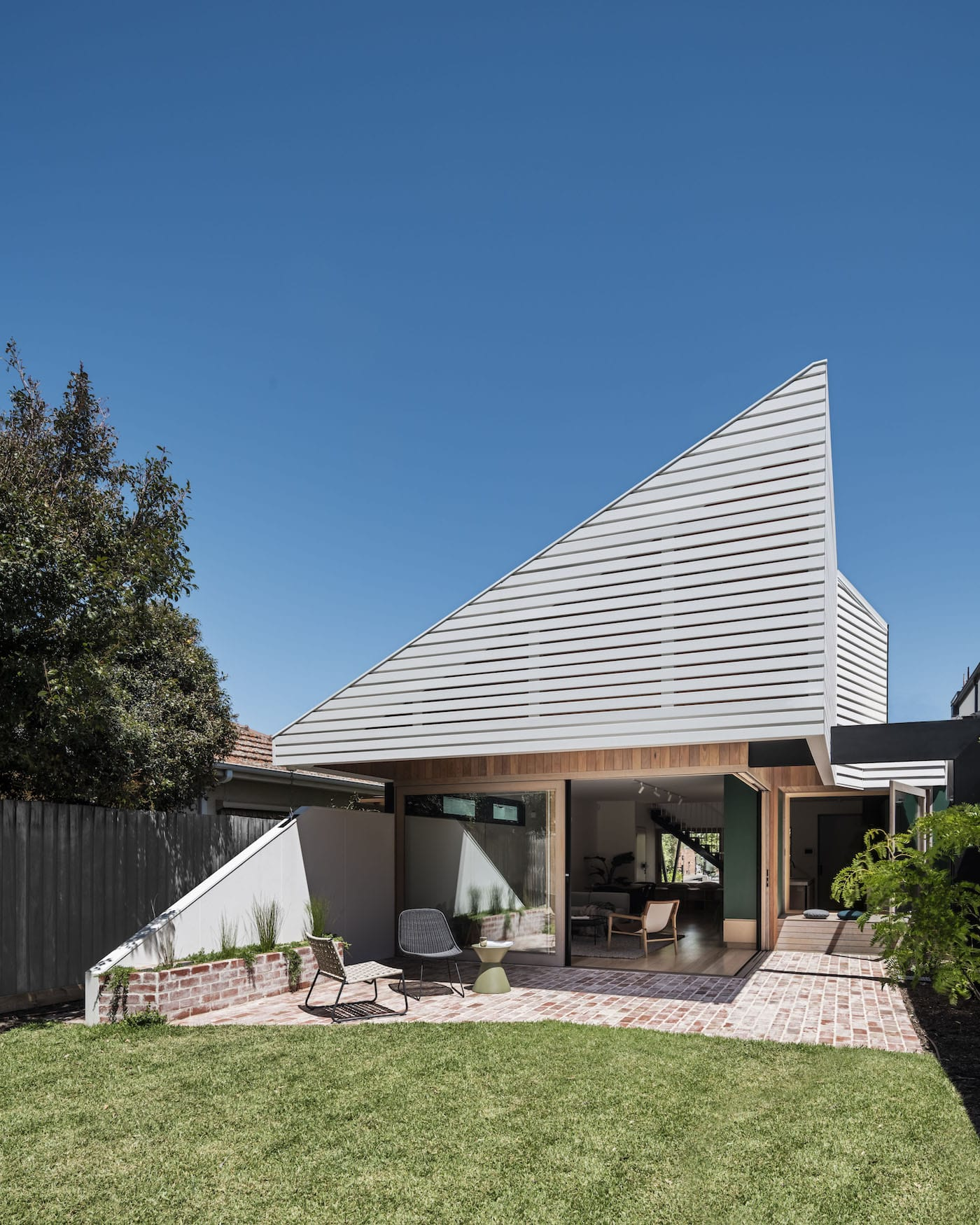 Rear view of eco friendly home with white timber slatted facade