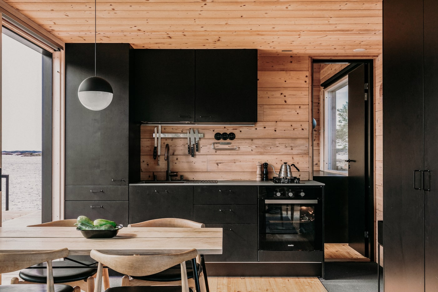 Kitchen with pine timber walls and black joinery