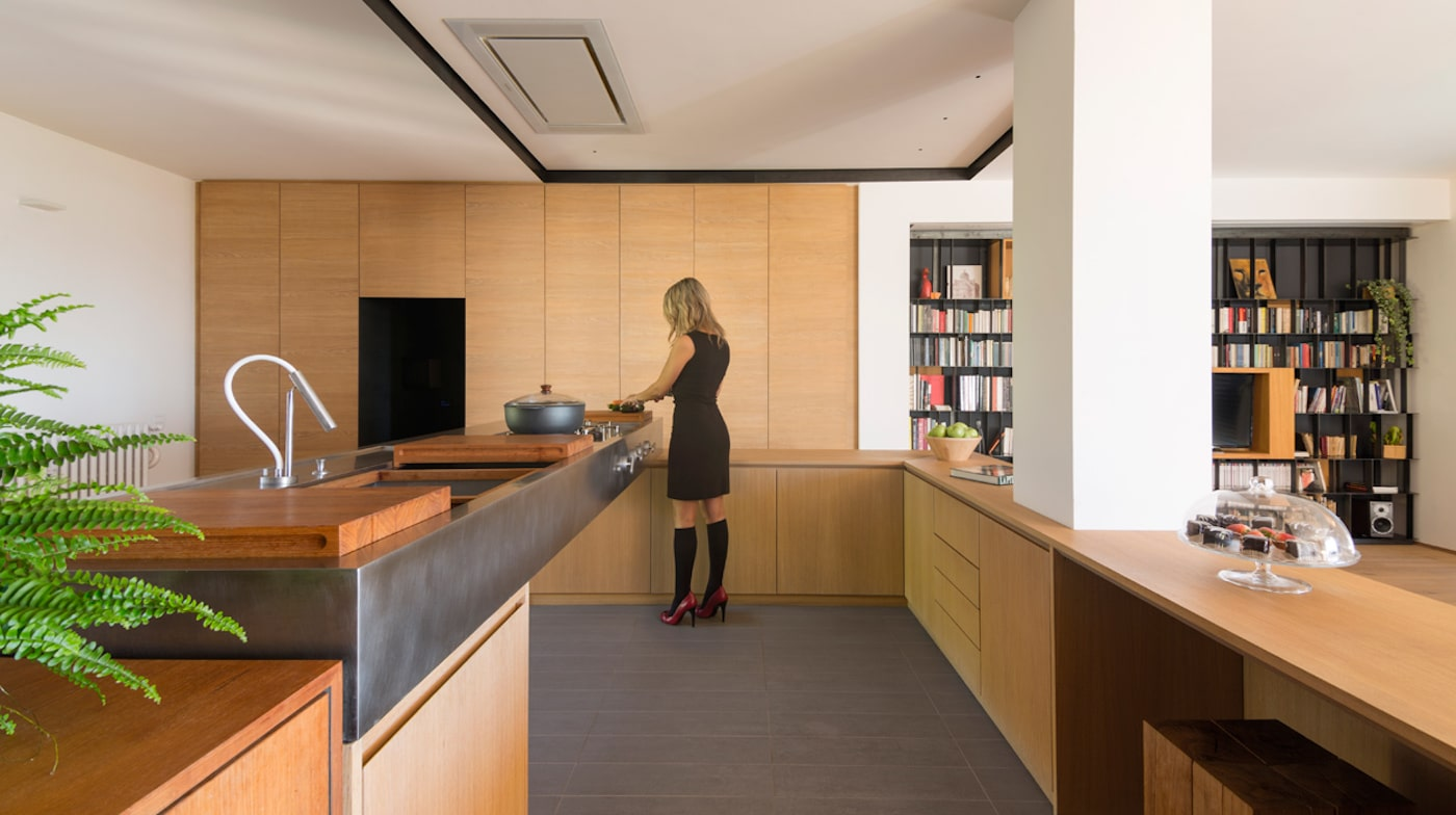 Woman in kitchen with timber cupboards