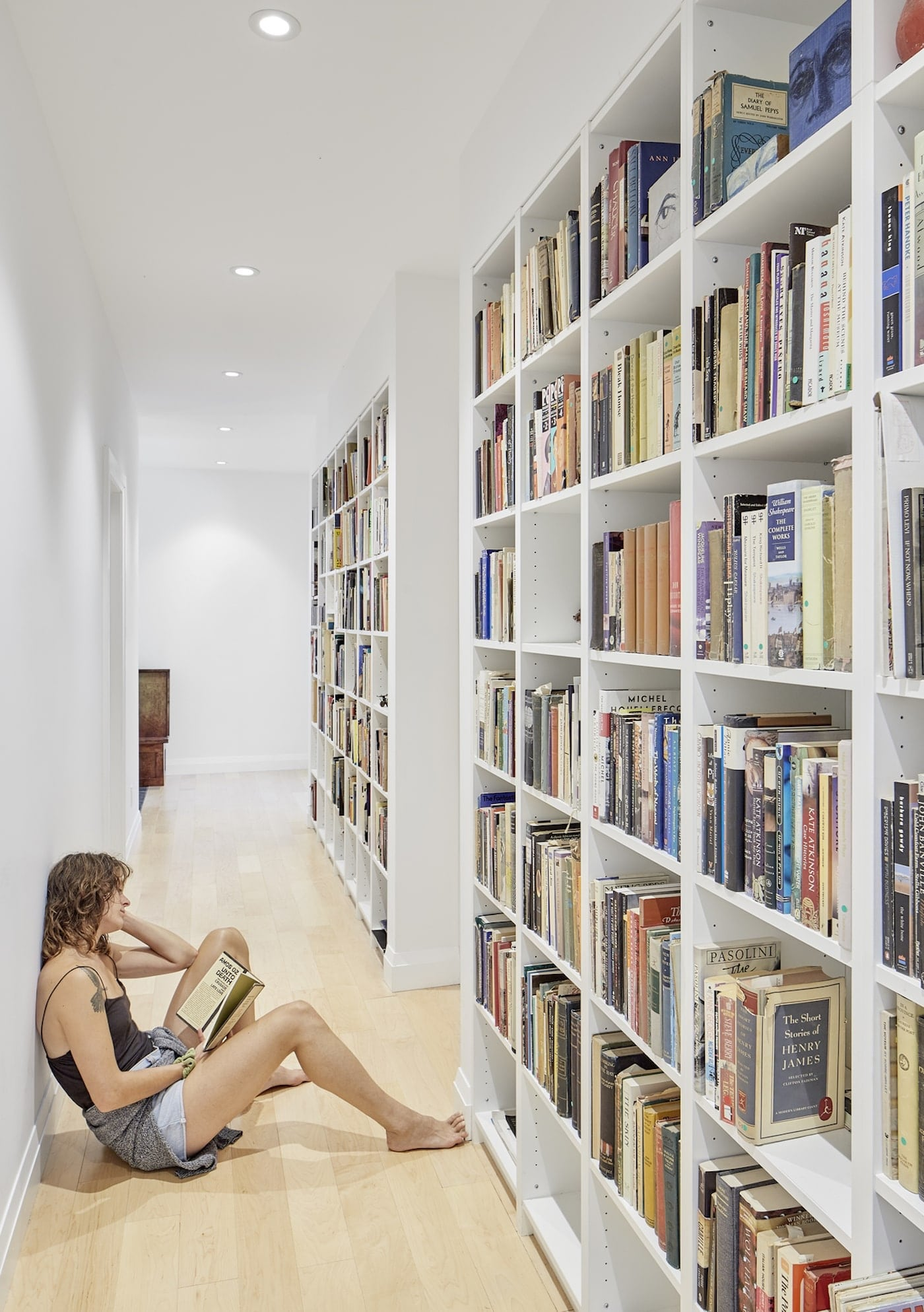 Woman sitting of floor of library in hallway reading a book