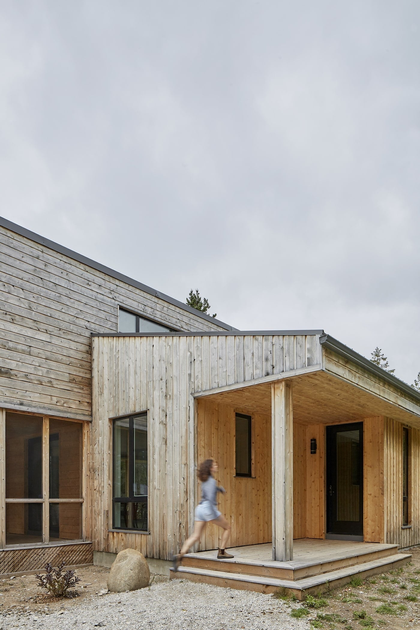 Woman walking onto front entry of timber off-grid sustainable house
