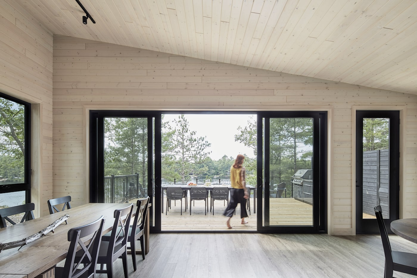 Woman walking on deck of all timber sustainable home