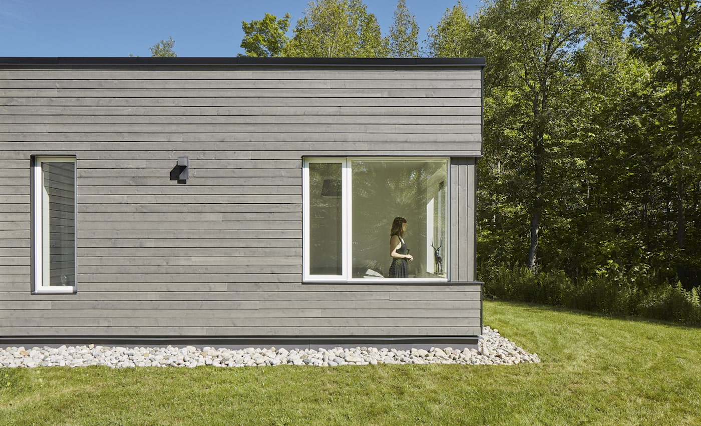 Woman standing in window of timber clad sustainable house design