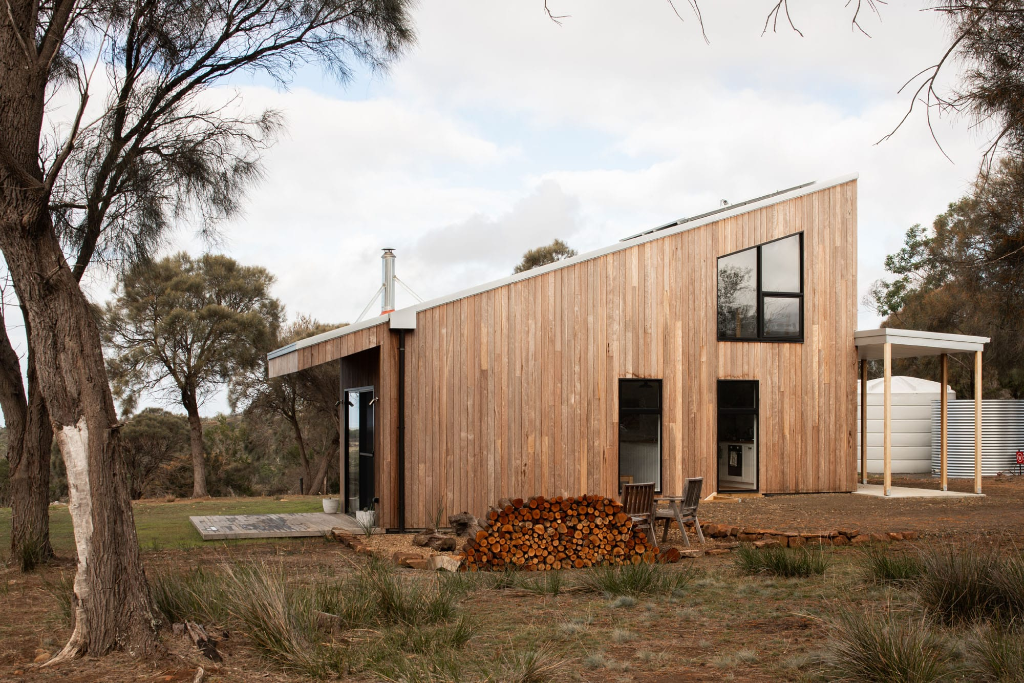 Side view of timber clad sustainable house and water tanks