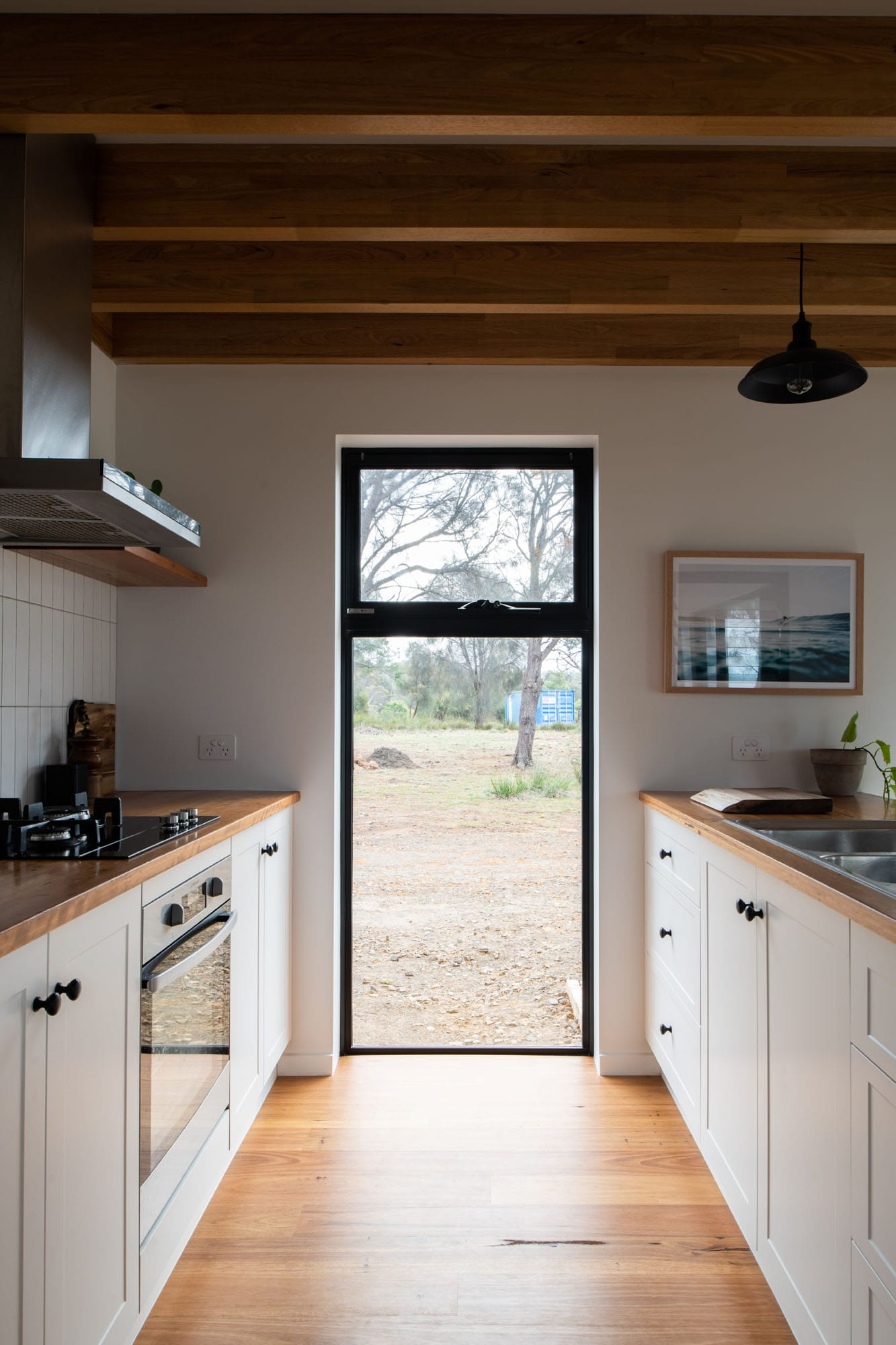 White kitchen cupboards and timber floor of sustainable house