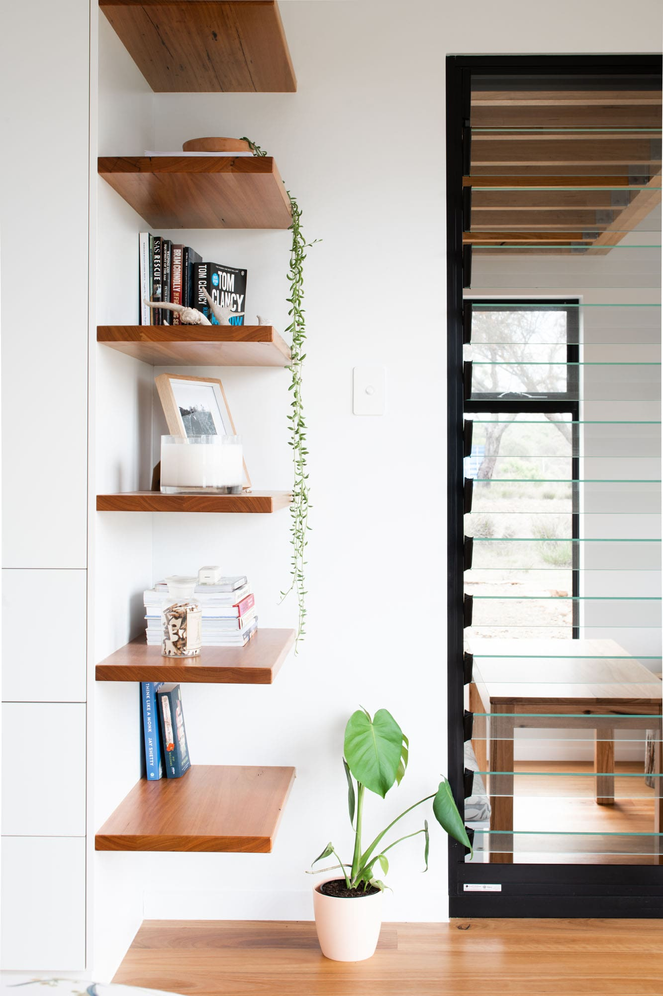 Timber shelves and louvered window in sustainable house