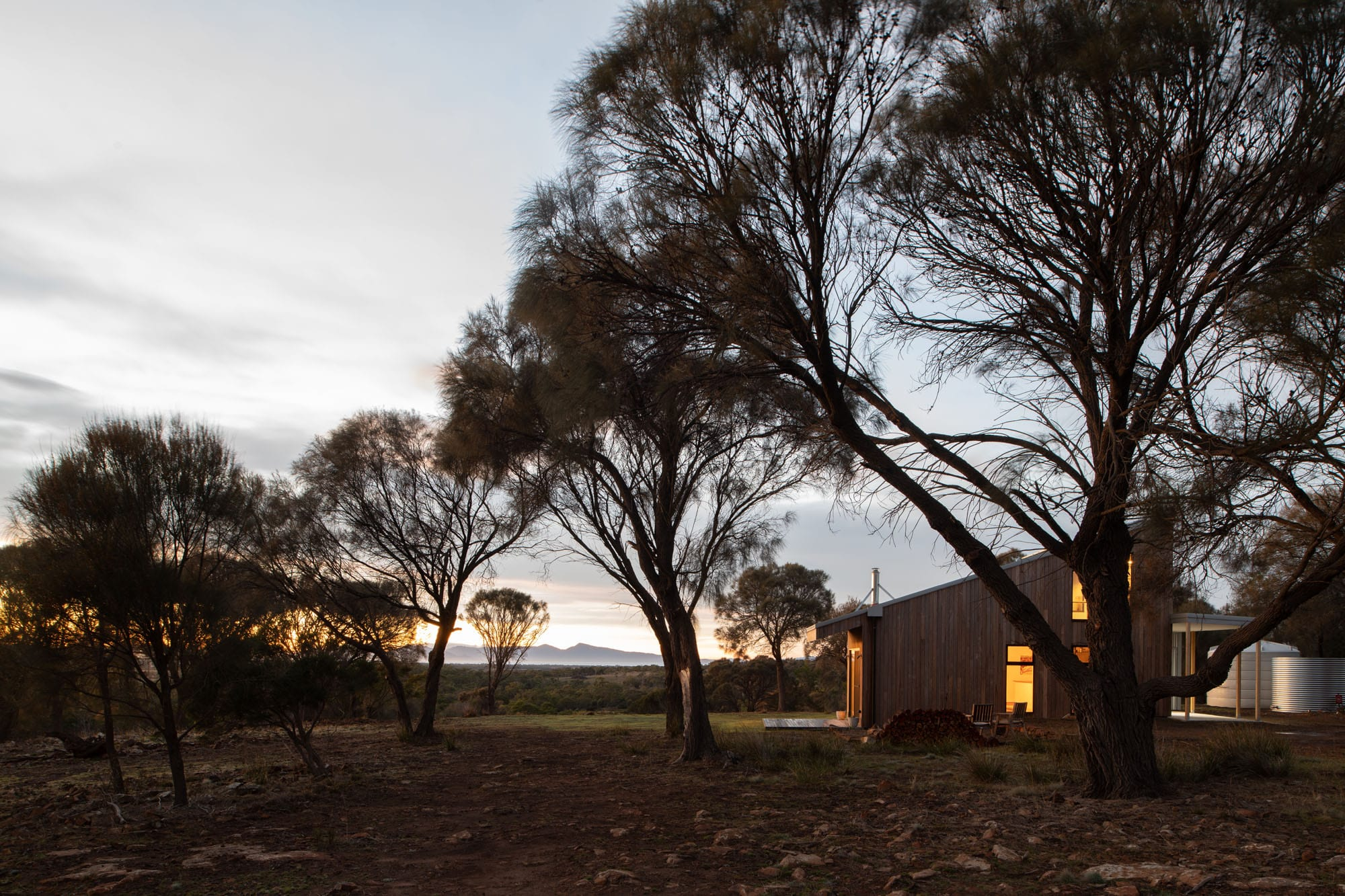 Distant view of timber off-grid sustainable home at dusk