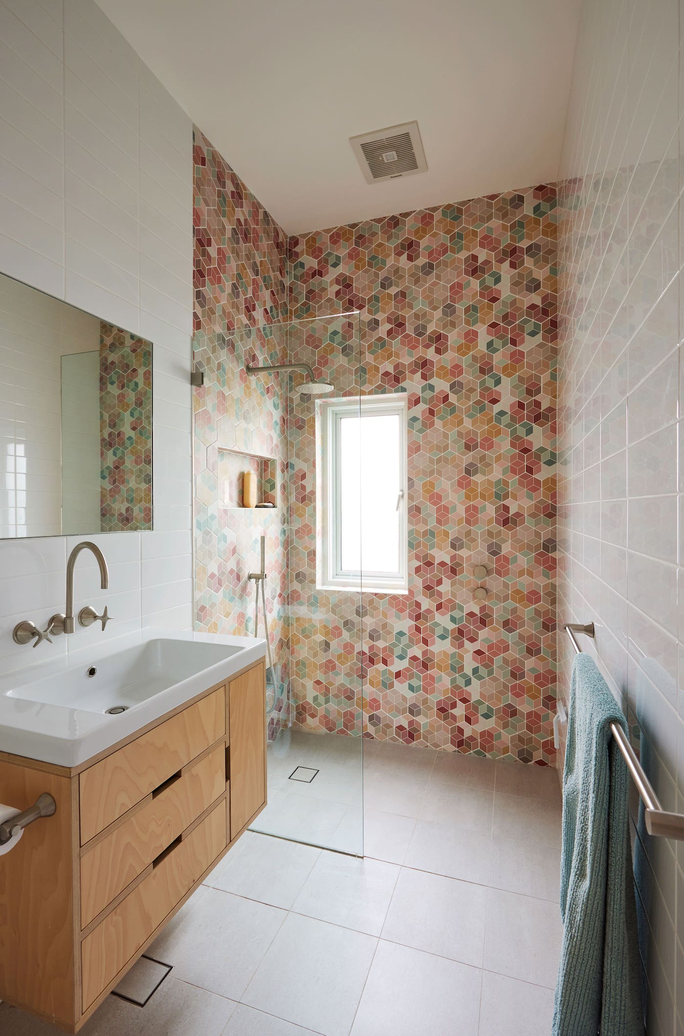 Timber bathroom vanity with bright shower tiles