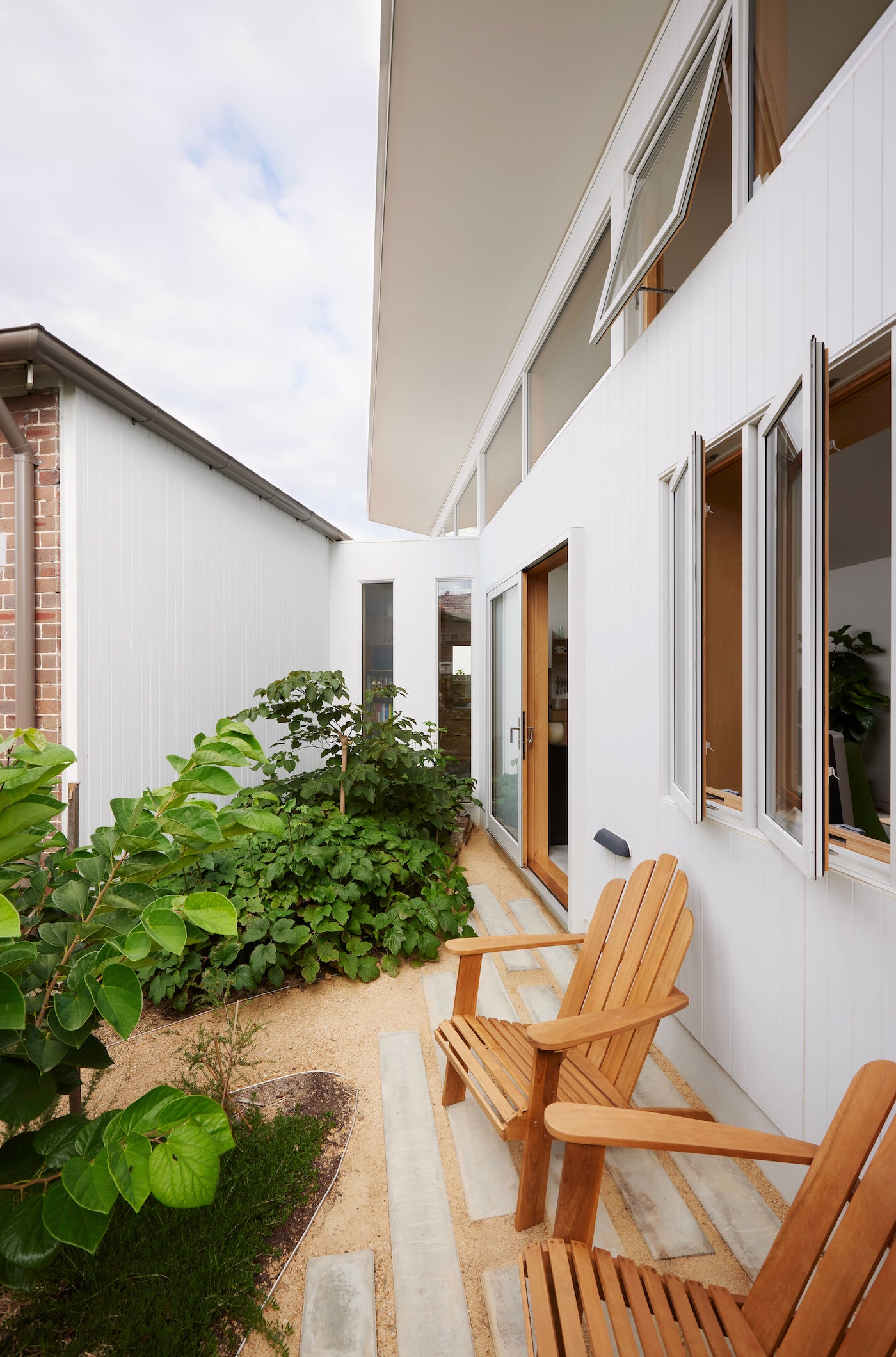 Timber chairs in front of sustainable new house addition