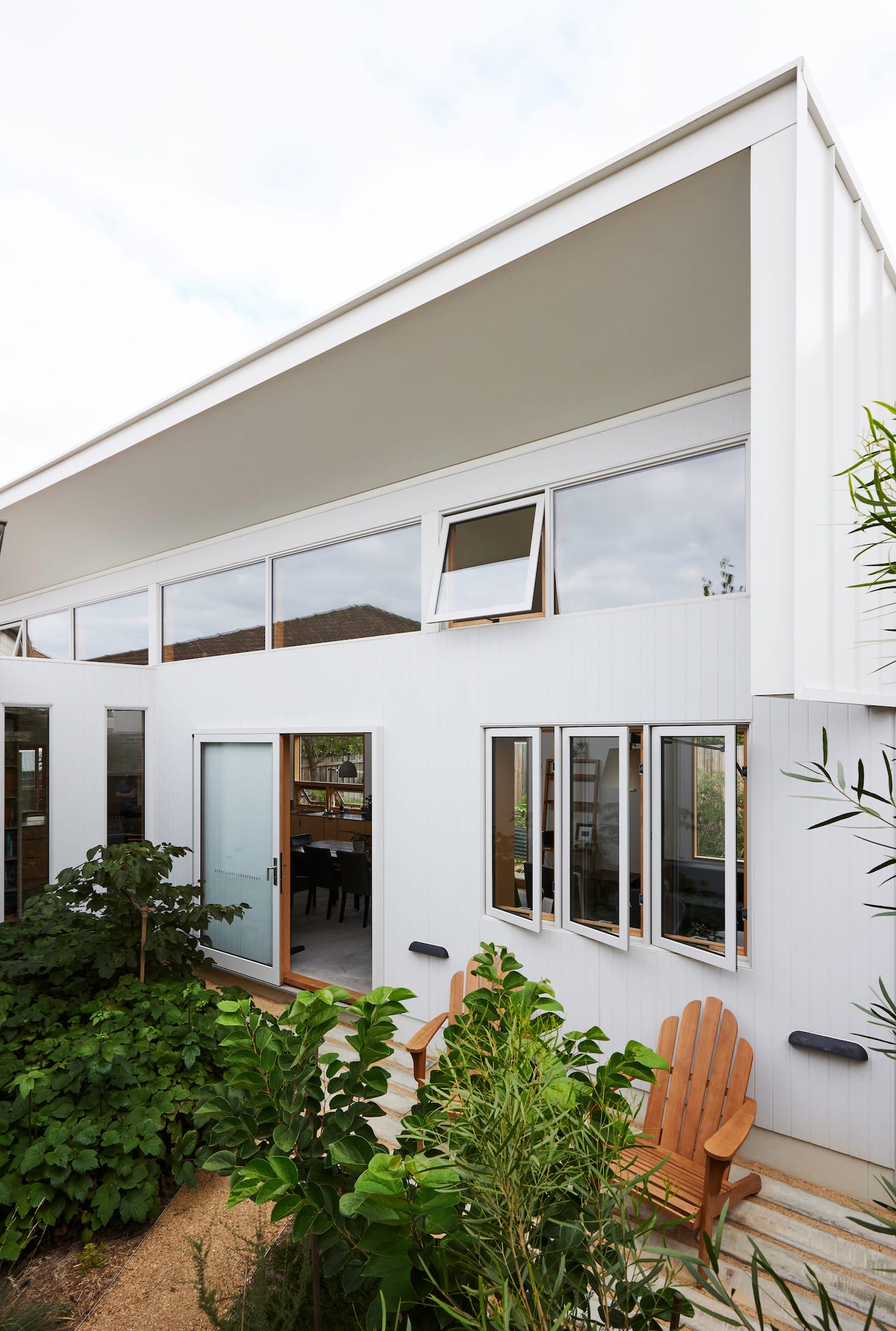 White facade of new addition with high windows
