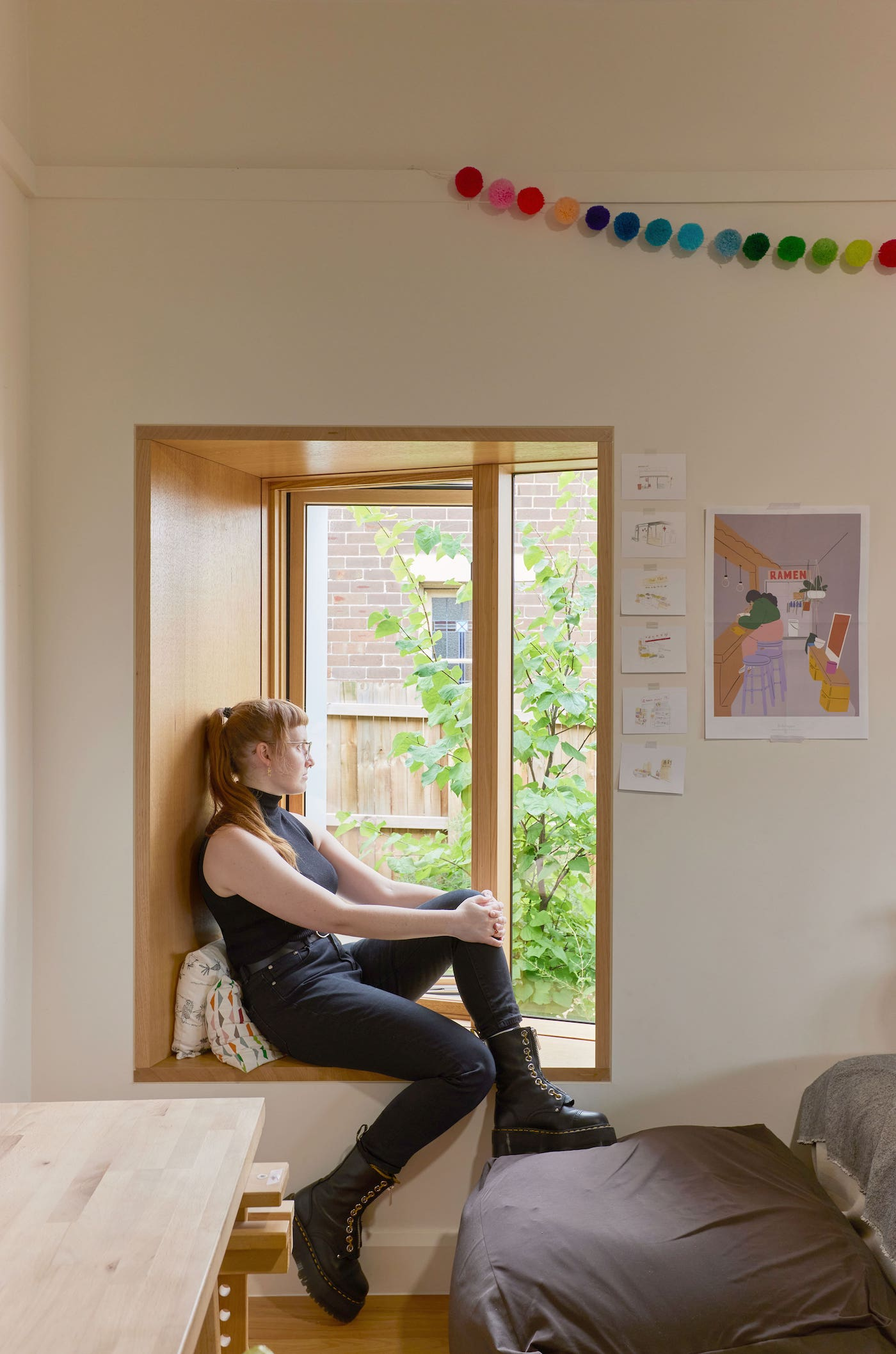 Woman sits on timber window seat looking at garden