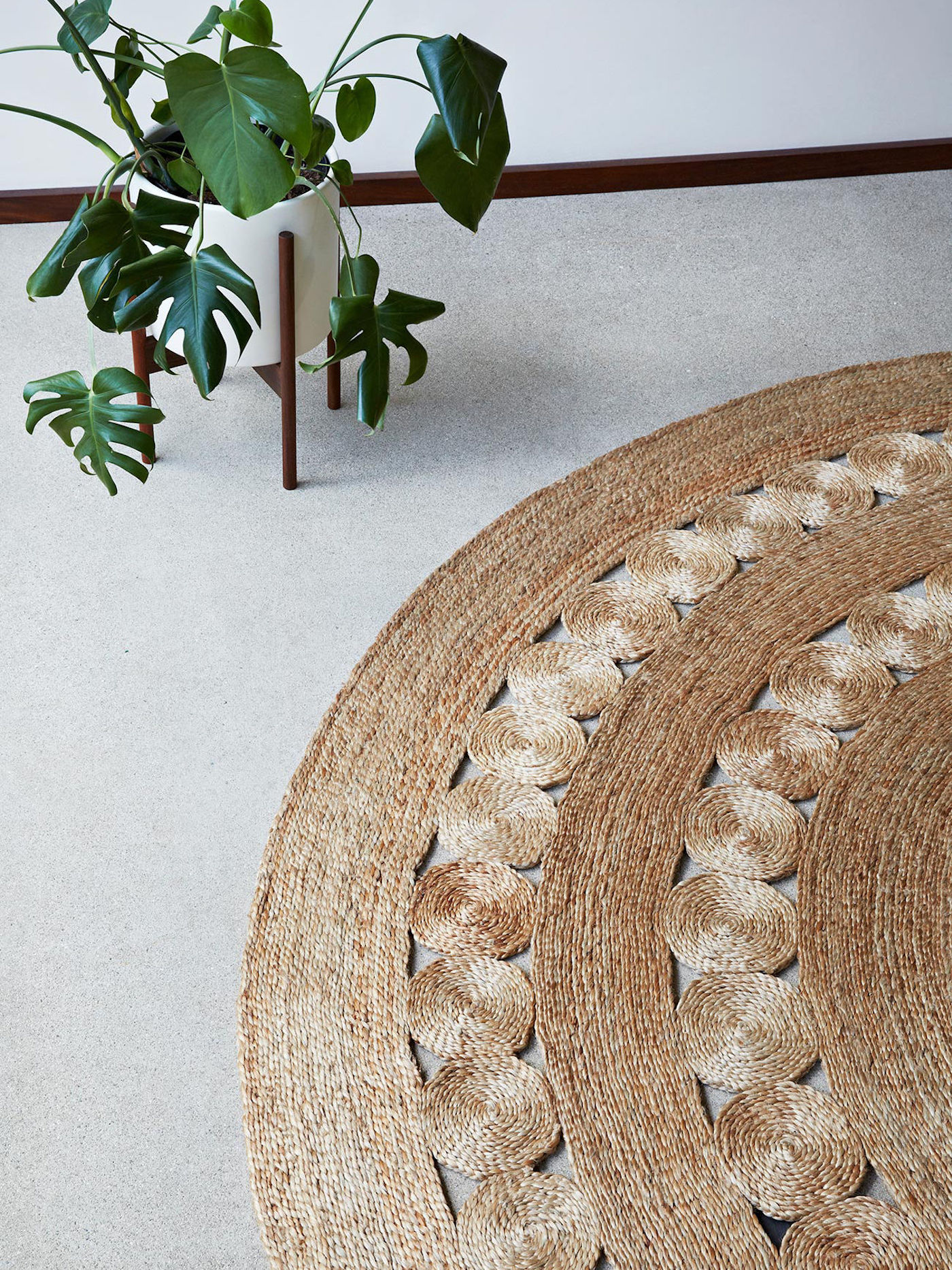 Round jute rug with plant on floor