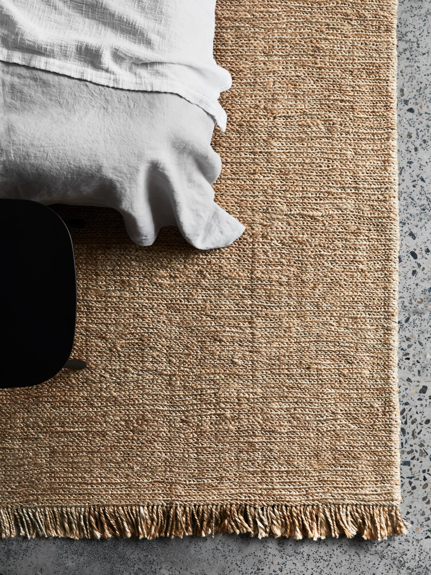Natural rug on concrete floor under bed