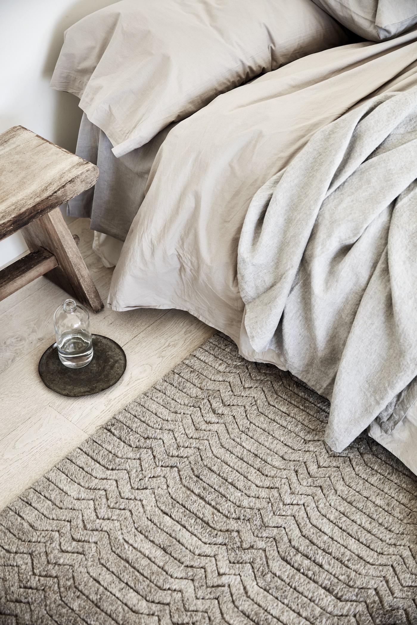 Grey rug on floor next to bed with grey bedlinen