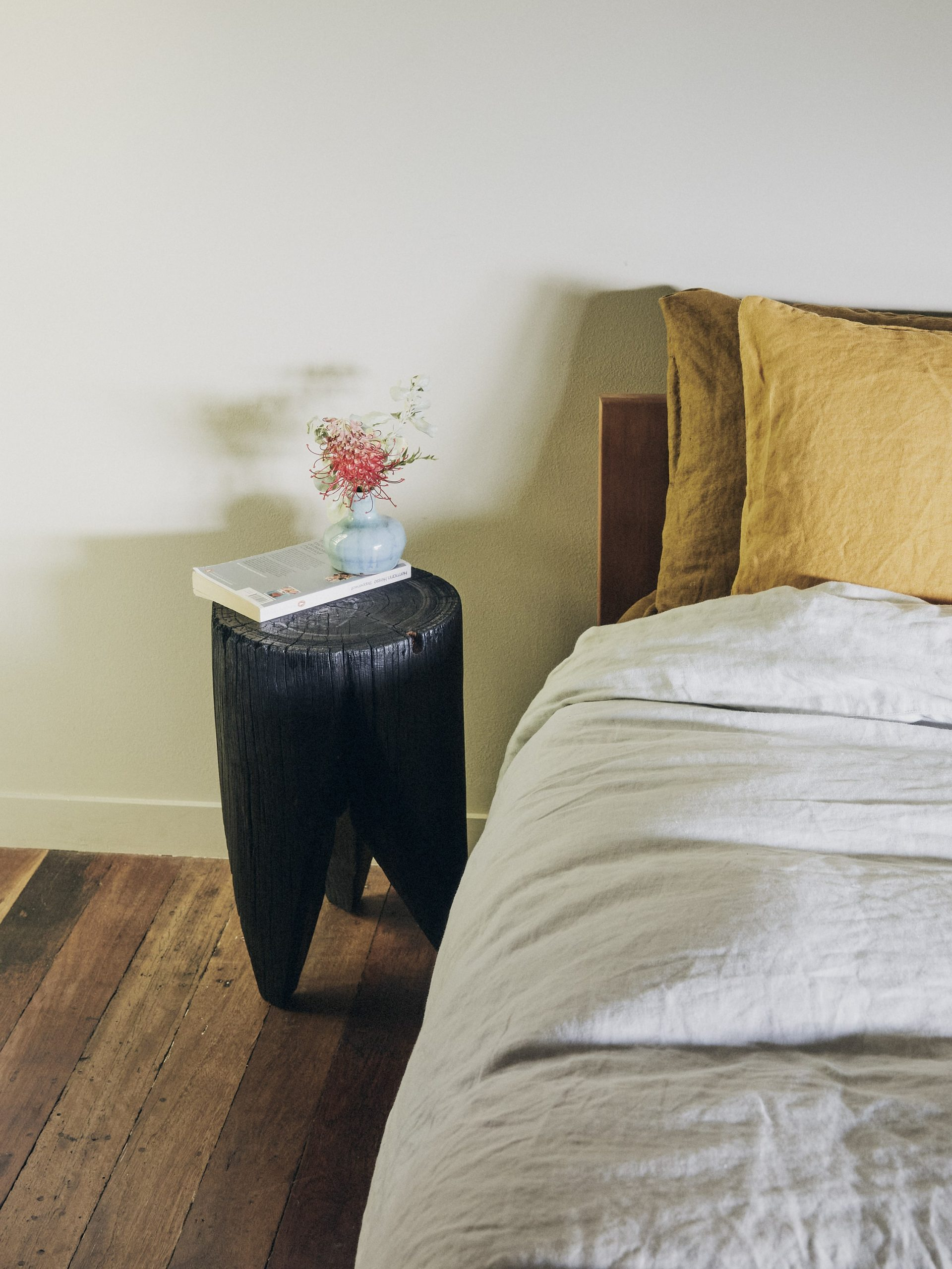 Black timber bedside table next to bed