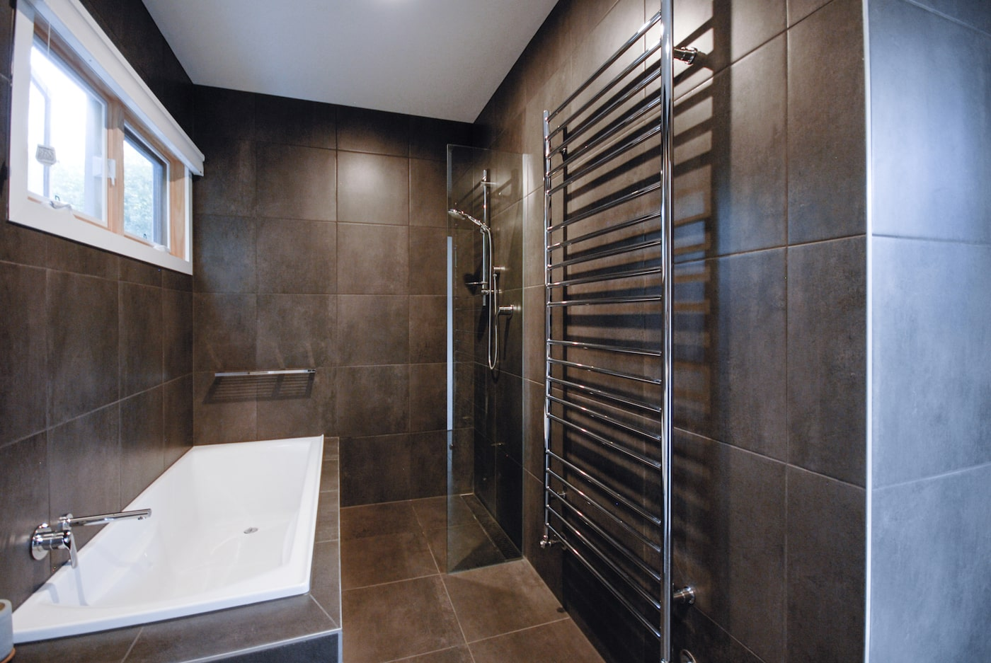 View of bath and shower with dark grey tiled walls and floor