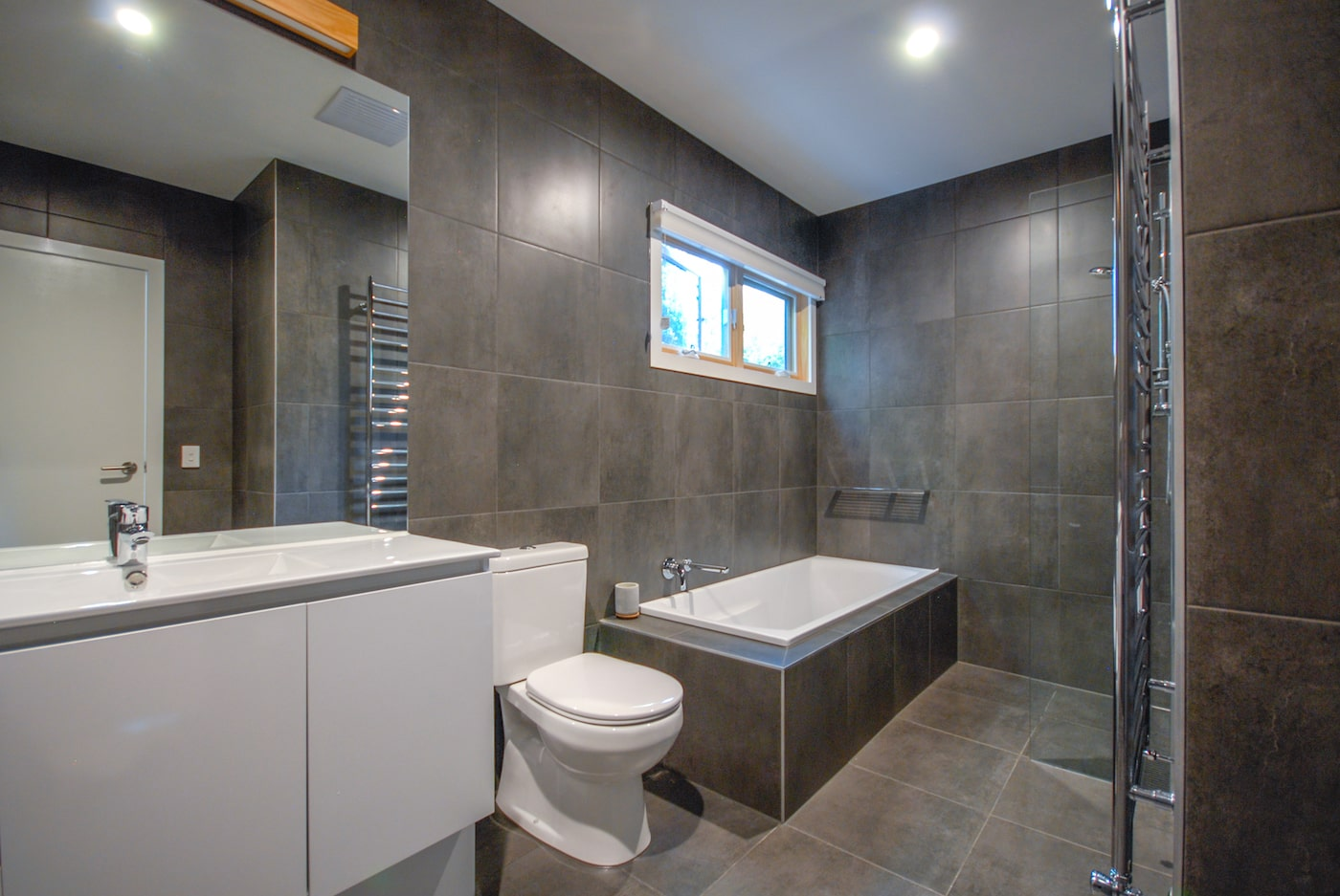 Dark grey tiled bathroom with white vanity