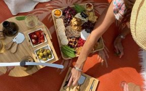 Women eating food from cheeseboard on picnic rug