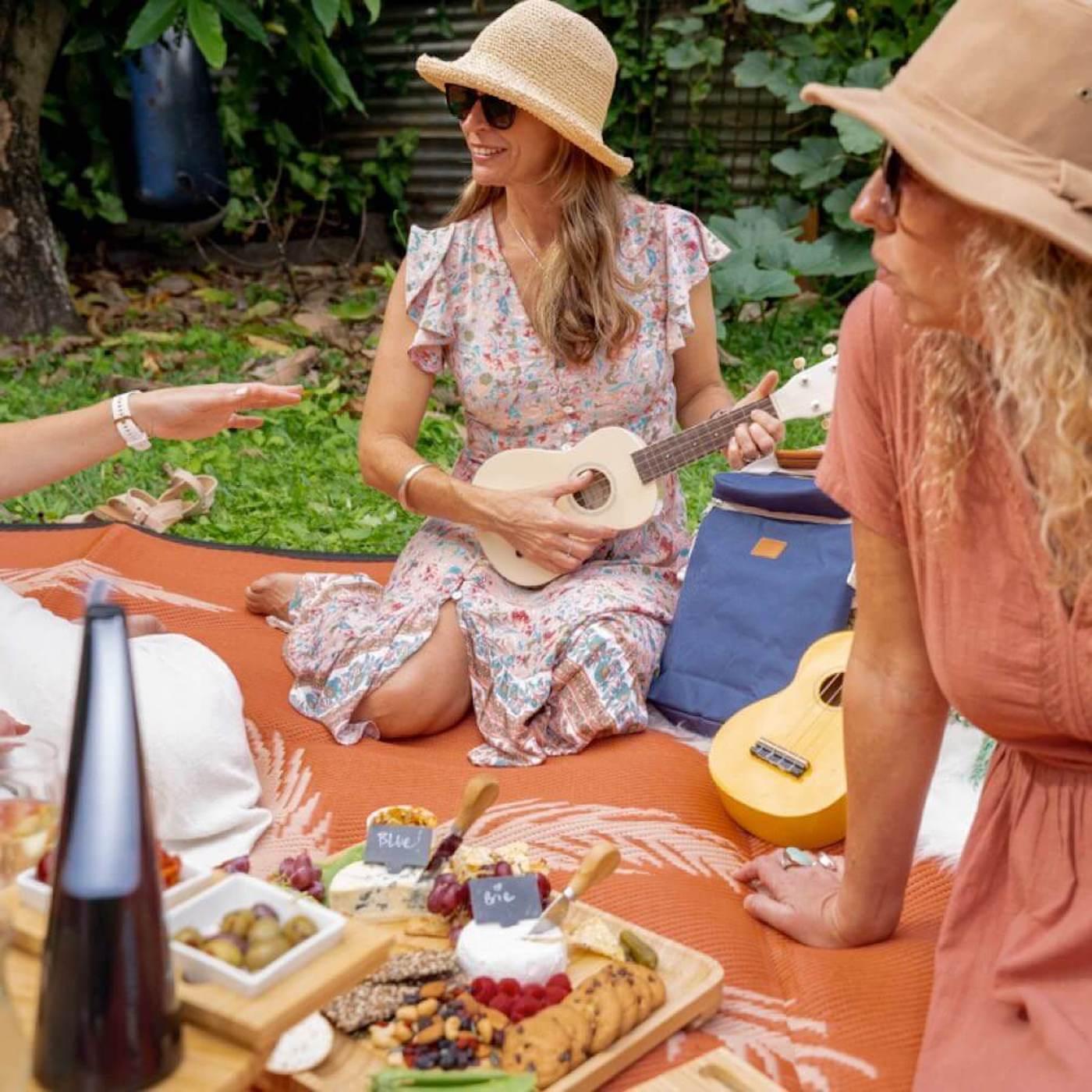 Women sitting on picnic rug around cheeseboard