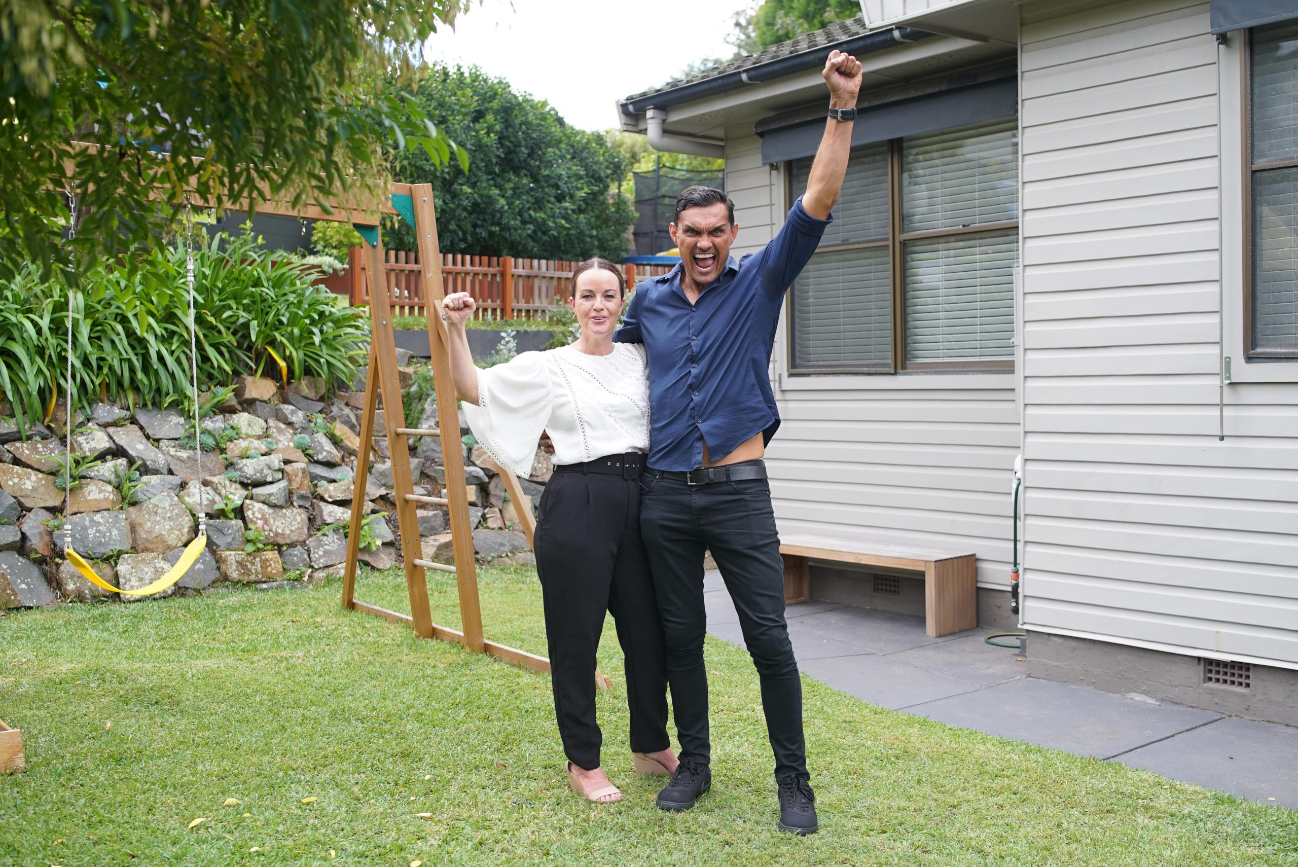 Couple standing in front of house with hands in air
