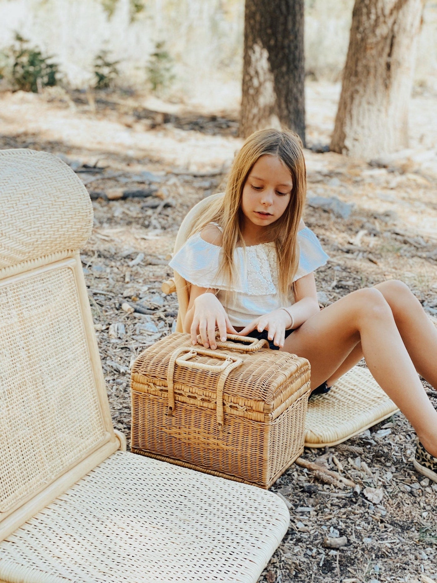 Girl sitting on rattan picnic chair