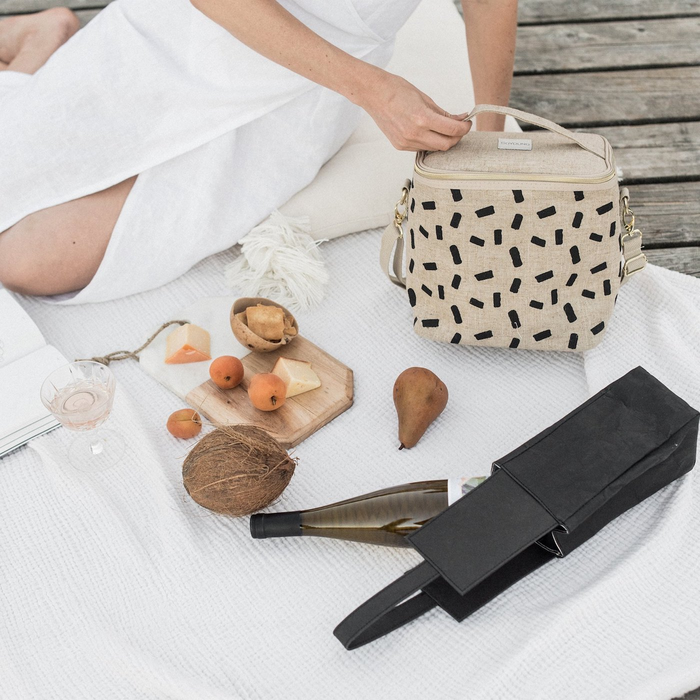Woman sitting on rug holding lunch cooler